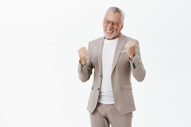 Succesvolle winnende bejaarde zakenman vuistpomp, verheugend op de overwinning