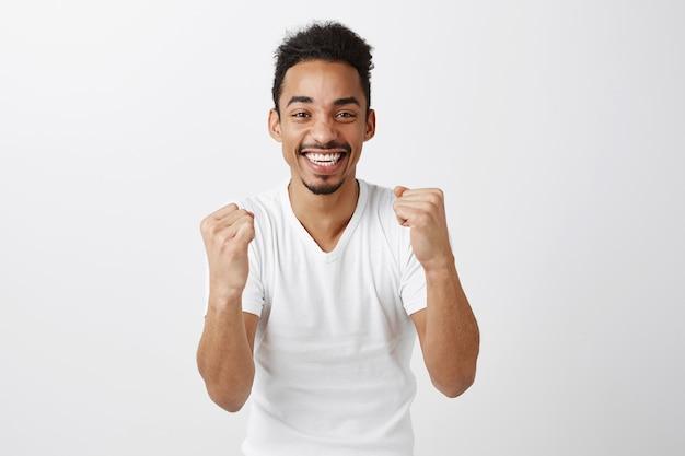 Succesvolle winnende donkere man die zich verheugt, vuistpomp en glimlachend, ja zegt, zegevierend