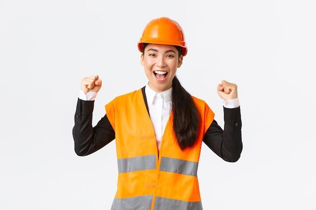 Succesvolle winnende vrouwelijke aziatische ingenieur vuistpomp en schreeuw ja opgetogen, draag een veiligheidshelm en -jas, triomfeert over de overwinning, voltooi het bouwen op tijd, staande tevreden witte achtergrond