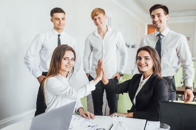 Succesvolle zakelijke bijeenkomst van jonge en mooie collega's op kantoor