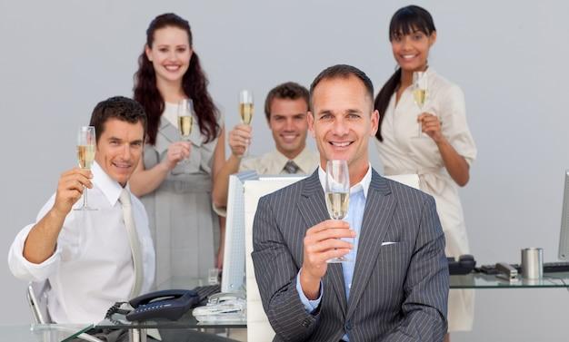 Succesvolle zakelijke collega's roosteren met champagne