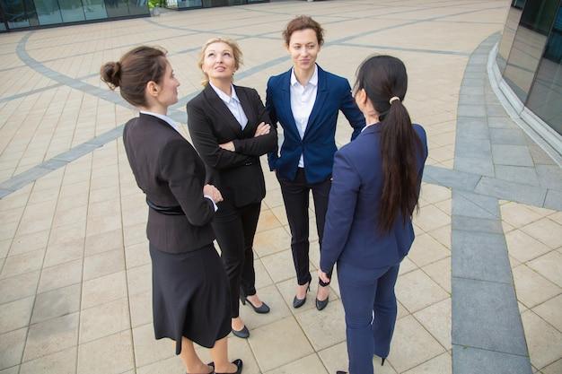 Succesvolle zakelijke dames praten buiten. onderneemsters die kostuums dragen die zich in stad verenigen. lage hoek. werk discussie en teamwerk concept