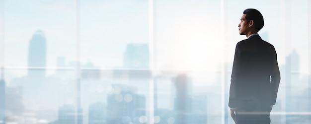 Succesvolle zakelijke manier, hoe succes te behalen en prestatie en focus te zijn op doelconcept, jonge zakenman die staat en uitkijkt om het beroepsleven te ontwikkelen tot leider op de top van de stad