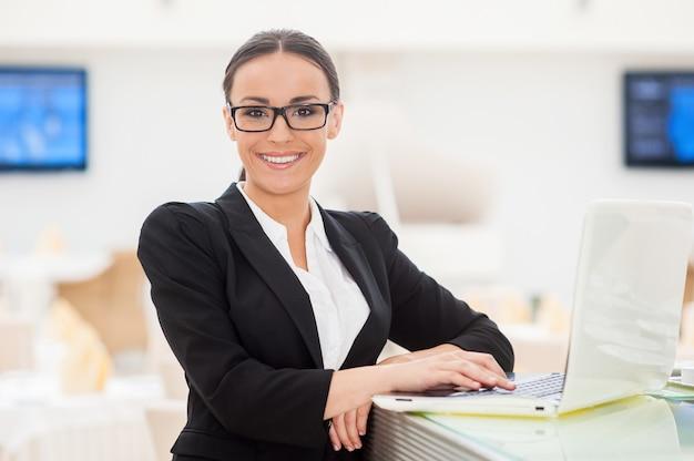 Succesvolle zakendame. mooie jonge vrouw in formalwear die aan laptop werkt en glimlacht terwijl ze aan de toog leunt