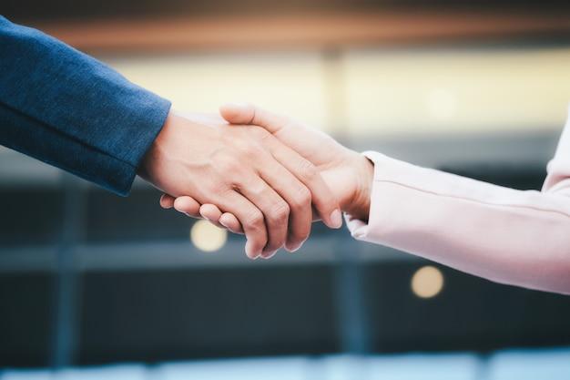 Succesvolle zakenlieden die na een goede deal handenschudden.