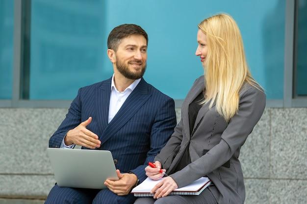 Succesvolle zakenlieden man en vrouw met documenten en laptop in handen bespreken zakelijke projecten