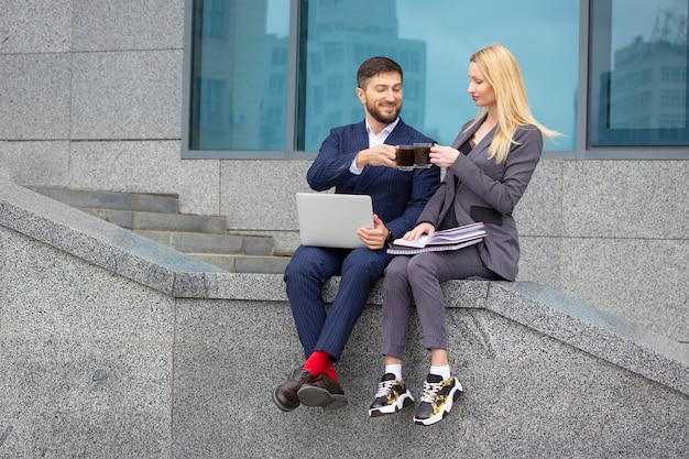 Succesvolle zakenlieden, man en vrouw zitten op de trappen van een bedrijfsgebouw met documenten en een laptop in hun handen, drinken koffie en bespreken een zakelijk werkplan