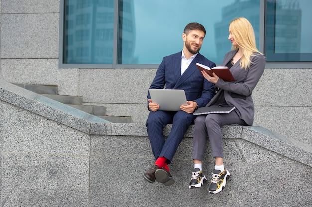 Succesvolle zakenlieden, man en vrouw zitten op de trappen van een bedrijfsgebouw met documenten en een laptop in hun handen om zakelijke projecten te bespreken