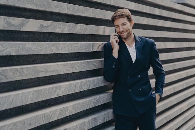 Succesvolle zakenman belt via smartphone tijdens werkonderbrekingsgesprekken met zakenpartner