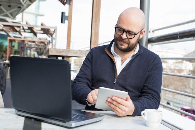 Succesvolle zakenman blijft werken tijdens koffiepauze