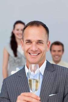 Succesvolle zakenman champagne met zijn team te houden