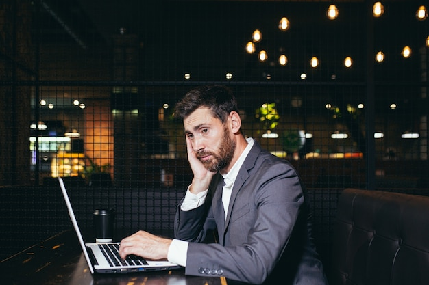 Succesvolle zakenman die aan laptop werkt tijdens de lunchpauze die in het restaurant van het hotel zit, moe van het doen van taak