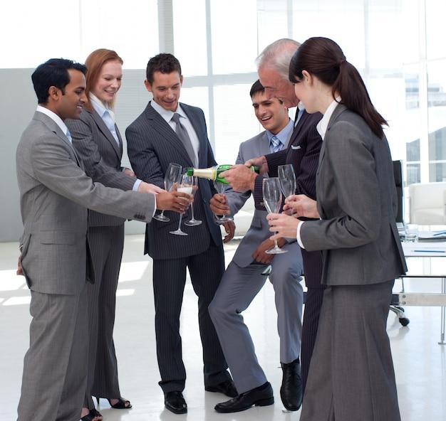Succesvolle zakenman die champagne dient aan zijn collega's