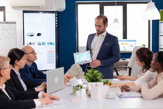 Succesvolle zakenman die de goede evolutie van het bedrijf presenteert met behulp van digitale tablet