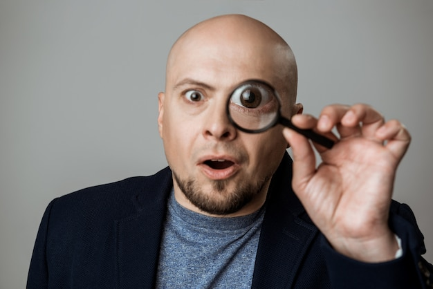 Succesvolle zakenman die door meer magnifier over beige muur kijkt.
