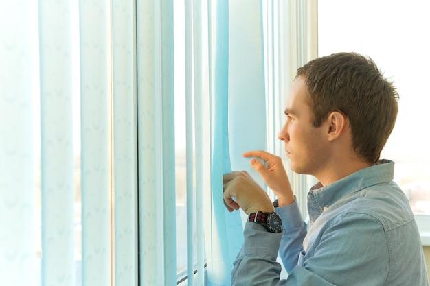 Succesvolle zakenman die ergens aan denkt terwijl hij bij het raam staat met jaloezieën, doordachte mannenondernemer gekleed in het blauwe shirt rustend. terugkijkend op het verleden