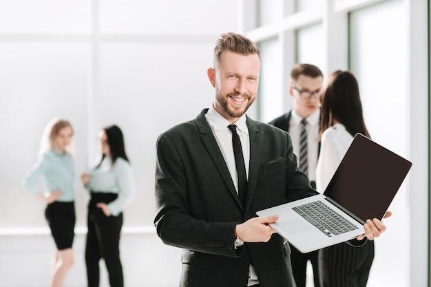 Succesvolle zakenman die financieel rapport op laptop scherm toont. foto met kopie ruimte