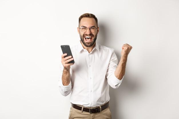 Succesvolle zakenman die gelukkig kijkt, vuistpomp en verheugt zich in het winnen van online loterij, staand.