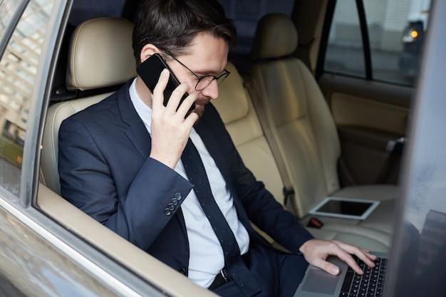 Succesvolle zakenman die in de auto werkt