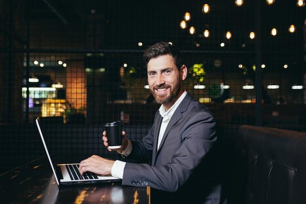 Succesvolle zakenman die op laptop werkt tijdens de lunchpauze die in een hotelrestaurant zit, een man die lacht en naar de camera kijkt met een kopje koffie