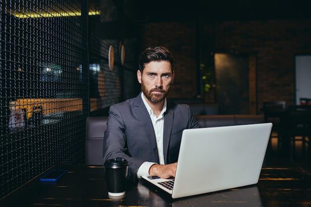 Succesvolle zakenman die op laptop werkt tijdens de lunchpauze die in het restaurant van het hotel zit en serieus naar de camera kijkt met een kopje koffie