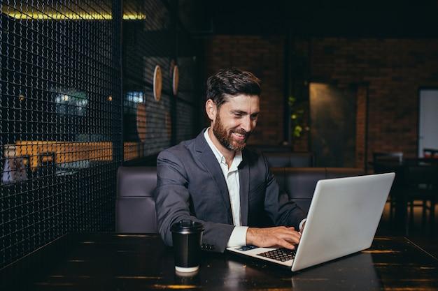 Succesvolle zakenman die op laptop werkt tijdens de lunchpauze in het restaurant van het hotel