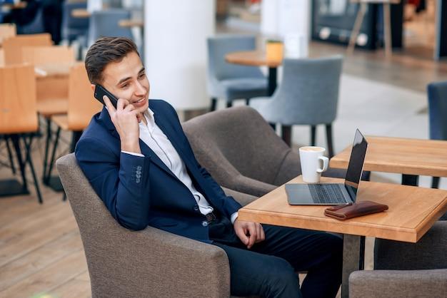 Succesvolle zakenman die op smartphone op zijn werkplaats met laptop, portefeuille en notitieboekje spreekt