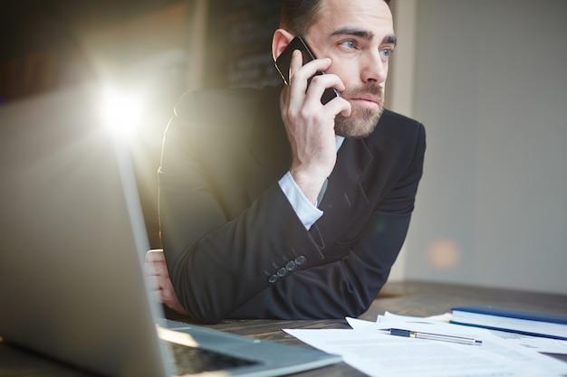 Succesvolle zakenman die telefonisch roept tijdens het werken