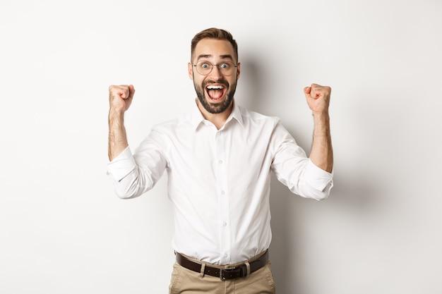 Succesvolle zakenman die zich verheugt, handen opheft en overwinning viert, iets wint