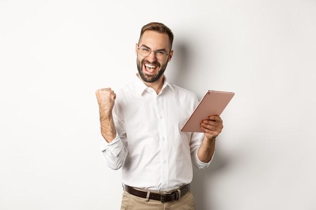 Succesvolle zakenman die zich verheugt over online winnen, lezen op digitale tablet en vuistpomp maken, triomferen, staande op een witte achtergrond.