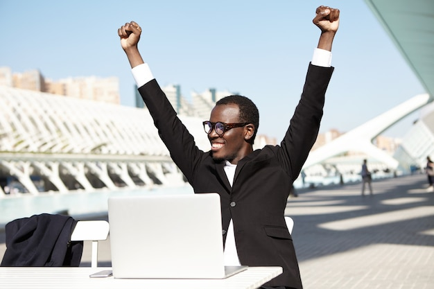 Succesvolle zakenman die zijn handen opheft die vrolijke uitdrukking hebben na ondertekening van contract