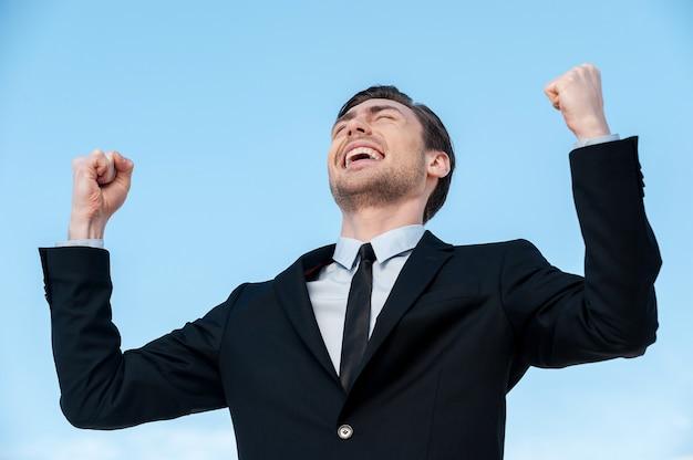 Succesvolle zakenman. gelukkige jonge man in pak gebaren terwijl hij buiten staat