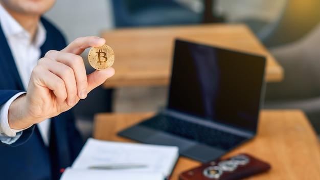 Succesvolle zakenman houdt een gouden bitcoin-muntstuk in zijn hand. cryptocurrency bedrijfsconcept