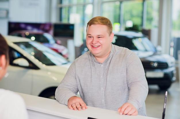 Succesvolle zakenman in autodealer - verkoop van voertuigen aan klanten