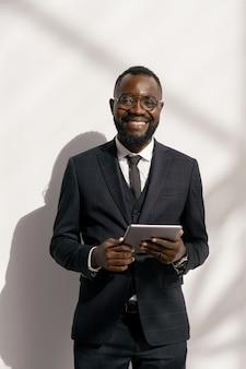 Succesvolle zakenman in elegant pak die naar je kijkt met een glimlach