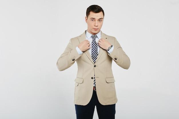 Succesvolle zakenman in het witte overhemd met een gestreepte stropdas, in een beige blazer en in een donkere spijkerbroek, geïsoleerd op een witte achtergrond