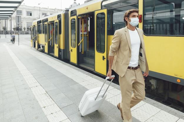 Succesvolle zakenman in trendy beige pak met werkreis. jong mannetje dat in medisch masker met witte koffer reist
