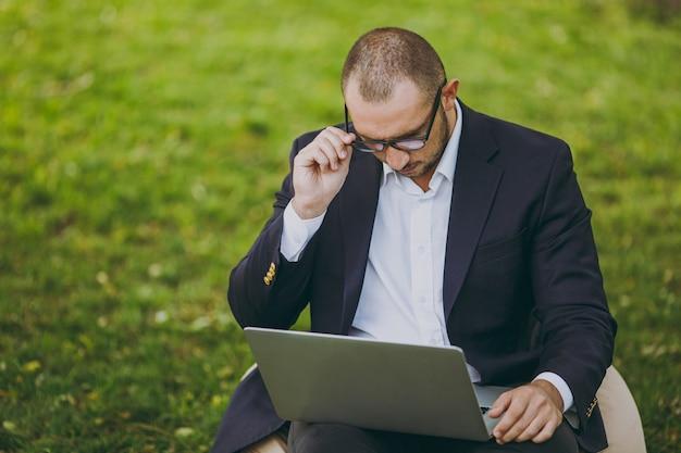 Succesvolle zakenman in wit overhemd, klassiek pak, correcte bril. man zit op zachte poef, werk op laptop pc-computer in stadspark op groen gazon buiten op de natuur. mobiel kantoor, bedrijfsconcept.