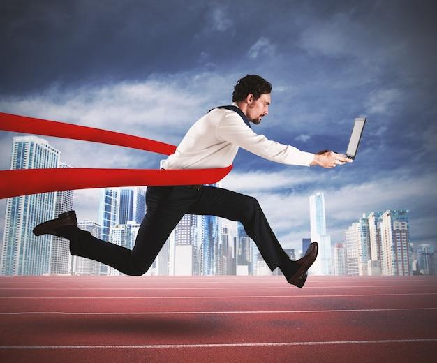 Succesvolle zakenman met de computer komt aan het einde van de race
