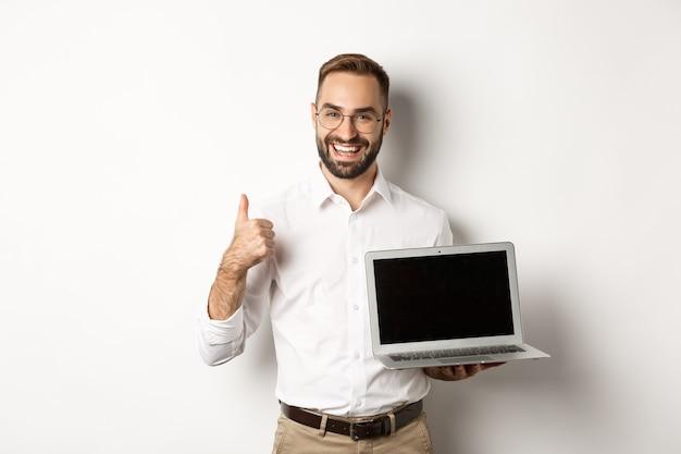 Succesvolle zakenman met laptopscherm, duim omhoog in goedkeuring, prijs iets goeds, staande op een witte achtergrond.