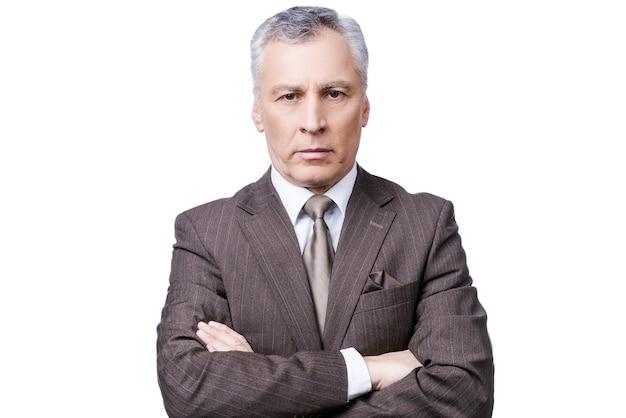 Succesvolle zakenman. portret van een zelfverzekerde volwassen man in formalwear die naar de camera kijkt terwijl hij zijn armen gekruist houdt en tegen een witte achtergrond staat