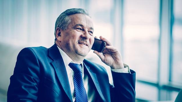Succesvolle zakenman praten op zijn smartphone zittend op de bank