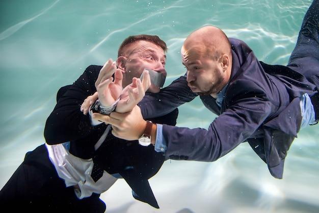 Succesvolle zakenman redt jonge start-up met zijn mond dichtgeplakt en zijn handen onder water vastgebonden