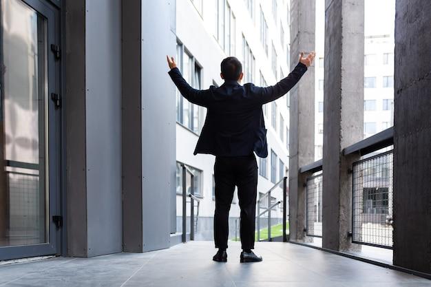 Succesvolle zakenman steekt zijn handen omhoog als een teken van overwinning en succes in de buurt van het achteraanzicht van het moderne kantoor