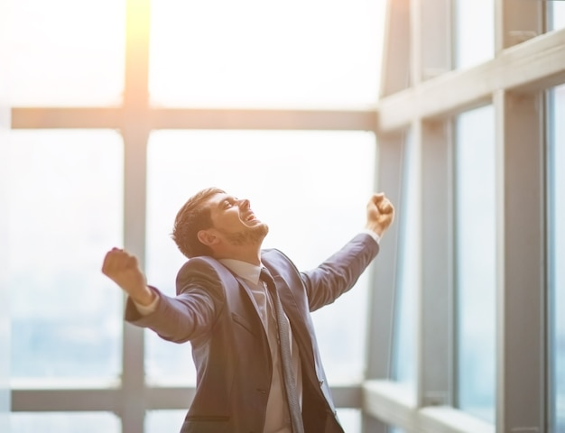 Succesvolle zakenman steekt zijn handen omhoog en viert overwinning