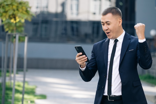 Succesvolle zakenman vieren wint met mobiele telefoon buiten