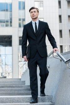 Succesvolle zakenman. volledige lengte van vrolijke jonge mannen in formele kleding met aktetas terwijl ze buiten wandelen