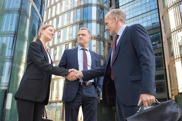 Succesvolle zakenmensen bijeen in stad, handen schudden in de buurt van kantoorgebouw. lage hoek geschoten. communicatie en partnerschap concept