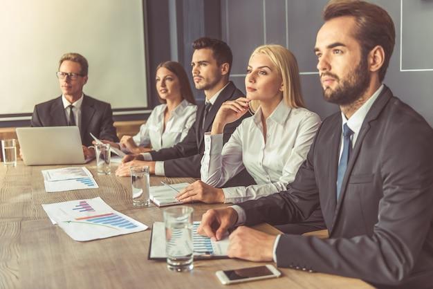 Succesvolle zakenmensen in formele slijtage luisteren.