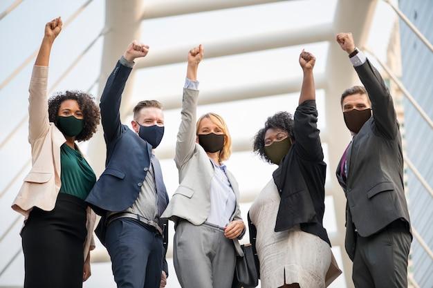 Succesvolle zakenmensen in masker tijdens covid 19 pandemin